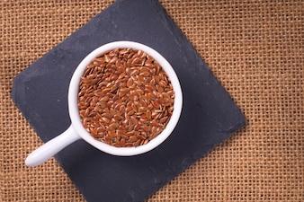 Nourriture saine Graines de lin bio en tasse blanche en céramique