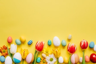Oeufs colorés lumineux avec des fleurs sur jaune