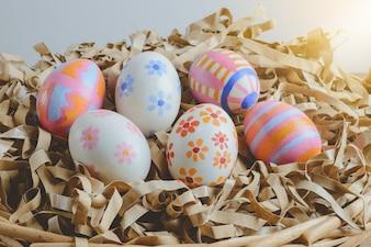 Oeufs de Pâques colorés à la main sur papier de paille dans le panier