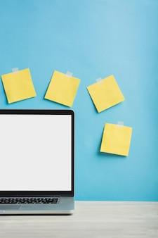 Ordinateur portable devant des notes adhésives jaunes collées sur un mur