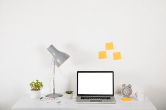 Ordinateur portable sur le bureau près des décorations et des notes autocollantes