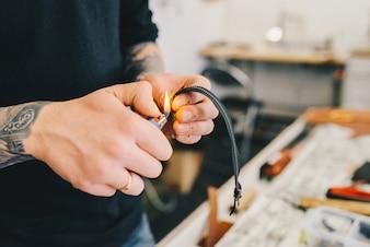 Ouvrier en cuir travaillant avec du cuir à l'aide d'un marteau.