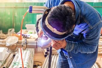 Ouvrier industriel avec masque de protection soudant une tuyauterie en métal à l'aide d'une soudeuse tig
