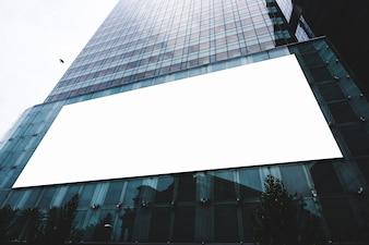 Panneau d'affichage vide sur un mur de bâtiment, avec vide pour bannière publicitaire.