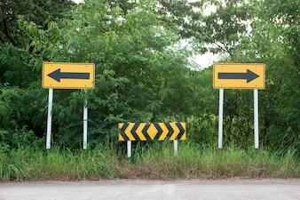 Panneau de signalisation. Les flèches jaunes au bout de la route pointant à gauche et à droite
