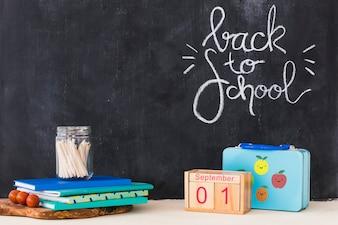 Papeterie et calendrier se trouvant près de la boîte à lunch et tableau noir