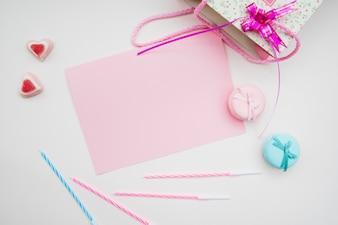 Papier rose les macarons; bougies et bonbons en forme de cœur et sac à provisions sur fond blanc