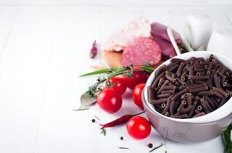 Pâtes sèches italiennes spiralées, tomates cerises rouges, saucisses, nature morte