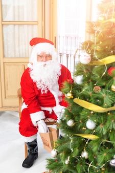 Père Noël mettant un cadeau sous un arbre de Noël