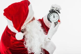 Père Noël regarde l'horloge dans les mains