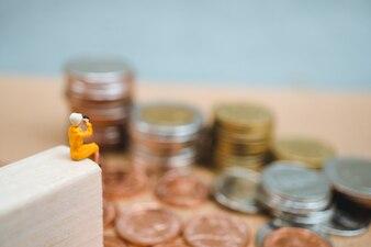 Personnes miniatures, femme qui cherche à empiler des pièces en utilisant le concept commercial et financier