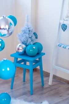 Petit arbre de Noël près de la chaise w
