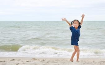 Petite fille asiatique agitant sa main en disant au revoir sur la plage