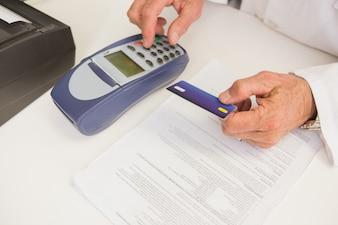 Pharmacien utilisant le clavier et détenant une carte de crédit