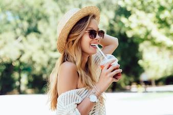 Photo d'été de belle femme joyeuse en lunettes de soleil, boire un cocktail frais de paille