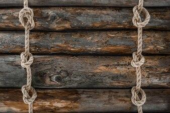 Plat poser avec des cordes marines arrangées avec des noeuds sur une table en bois grunge