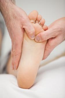 Podologue massant le pied d'un patient