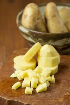 Pommes de terre et pommes de terre tranchées sur une table en bois. Mise au point sélective