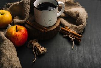 Pommes et cannelle près de boisson et de tissu