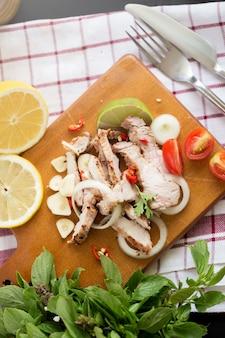 Porc tranché avec sauce épicée au citron et ail et chili sur planche de bois