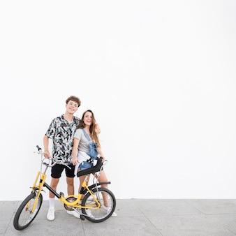 Portrait d'un couple heureux avec vélo debout sur le trottoir