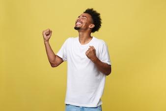 Portrait d'un jeune homme gai criant avec les bras levés en succès