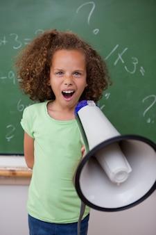 Portrait d'une jeune écolière hurlant dans un mégaphone dans une salle de classe