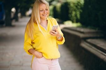Portrait de belle fille blonde parlant au téléphone