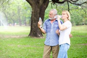 Portrait de couple de personnes âgées debout l'eau potable dans le parc