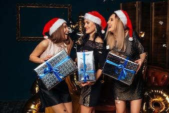 Portrait de trois jeunes femmes souriantes en chapeau de père Noël avec un cadeau dans les mains.