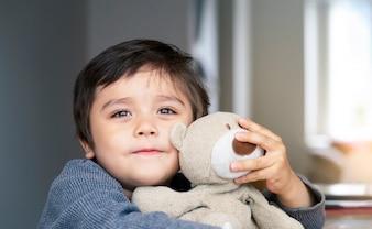 Portrait garçon mignon pose sa tête sur un ours en peluche et regarde avec de beaux yeux bruns