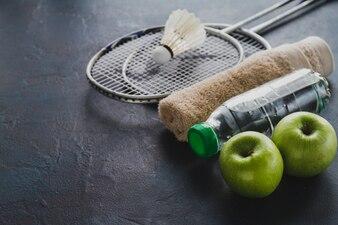 Raquettes de badminton avec des pommes et une bouteille d'eau
