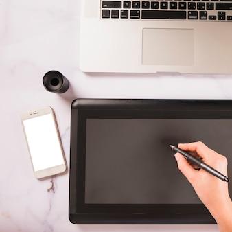 Recadrer la main à l'aide d'une tablette graphique près d'un smartphone et d'un ordinateur portable