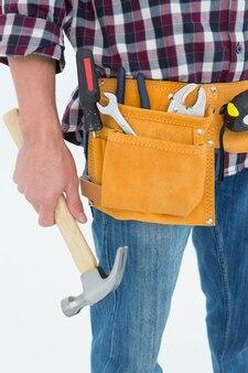 Réparateur portant la ceinture à outils tout en tenant le marteau