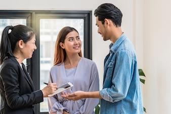Représentant de vente offre la liste des prix de la maison et les conditions pour l'achat ou la location de la maison