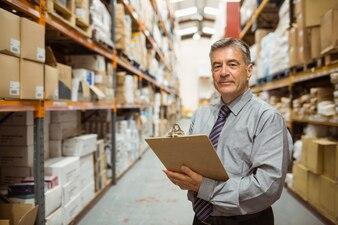 Responsable d'entrepôt souriant tenant un presse-papiers