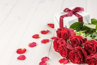 Roses rouges et coffret sur une table en bois blanche.