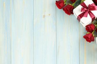 Roses rouges et coffret sur une table en bois bleu clair, vue de dessus.