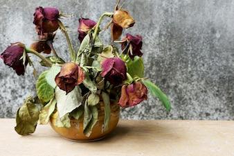 Roses sèches dans un gilet sur la table en bois avec le vieux fond de tache