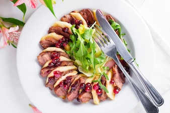 Salade avec des tranches de magret de canard aux pommes et salade à la sauce de myrtille