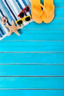 Scène de plage avec serviette rayée bleue, étoile de mer, coquillage, tongs et lunettes de soleil