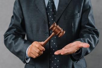 Section médiane d'un avocat tenant un maillet en bois à la main