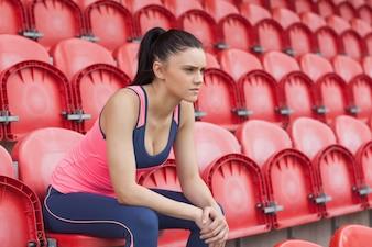 Sérieux tonique jeune femme assise sur une chaise dans le stade