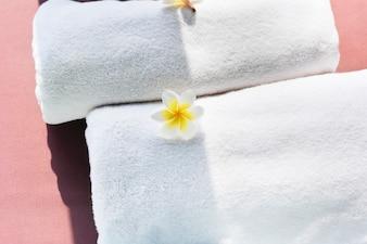 Serviettes blanches décorées de fleurs de plumeria