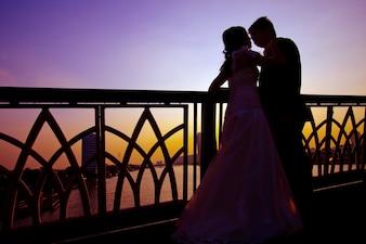 Shilhouette de couples de romantisme et de bonheur sur le pont sur la rivière