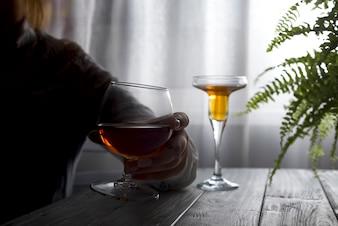 Silhouette de femme alcoolique anonyme, buvant derrière un verre d'alcool.