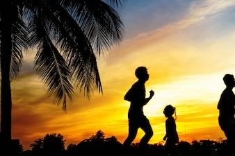 Silhouette de personnes faisant du jogging pour l'exercice au coucher du soleil.