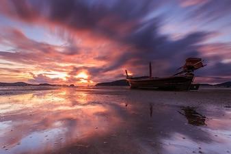 Silhouettes de bateau longtail et le lever du soleil à Phuket, en Thaïlande