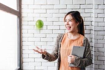 Soft Focus de jeune femme jetant une pomme tout en maintenant le sourire Tablet