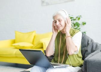 Souriant femme senior écoute de la musique sur le casque avec un ordinateur portable sur ses genoux